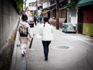 Geisha with maid and waiting car.