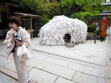 Rock shrine, Kyoto, covered in hand-written dreams. Climb through the hole in the rock to end a bad relationship.